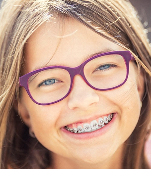 A young girl wearing purple glasses smiles while showing off her new braces put into place by her orthodontist in Plano