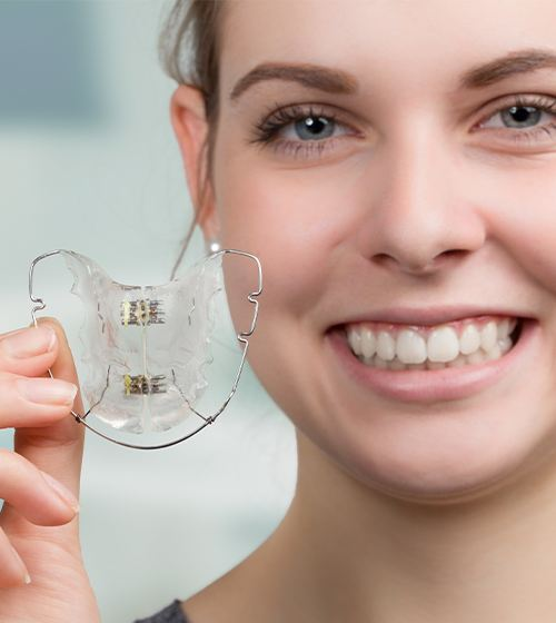 Woman holding retainer orthodontic appliance
