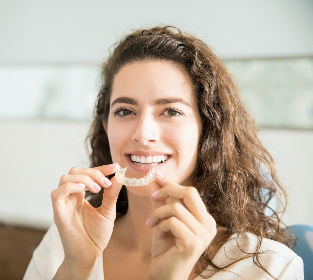 Woman placing adult orthodontics clear alignment tray
